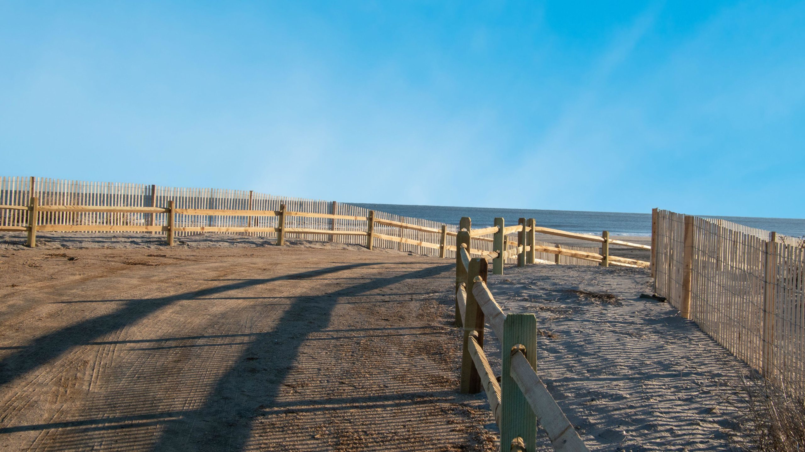 Curved sandy path to the ocean and beach lines with a wooden split rail fence and an erosion slat fence